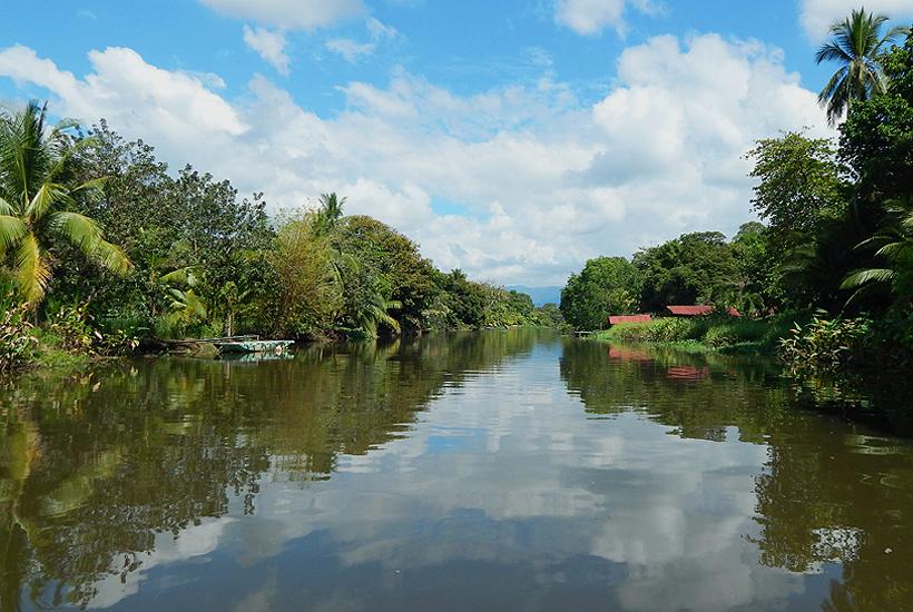 wolken weerkaatsen in Sierpe rivier met jungle langs oevers