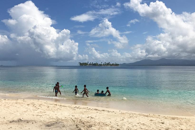 Kuna kinderen spelen in zee op eiland Naranjo Chico San Blas